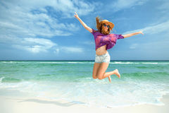 Woman jumps for joy on white sand beach. Young woman or teenager jumping for joy on a white sand beach with ocean waves and bright blue sky Royalty Free Stock Image