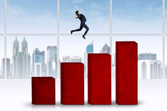 Woman jumps over business graph Royalty Free Stock Photography