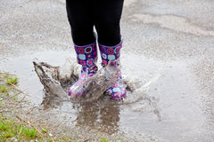 A woman jumps into a rain water puddle with rubber boots Stock Photography