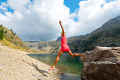 Woman jumps from a rock near a mountain lake stock images