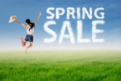 Woman jumps with spring sale cloud. Woman jumping over green meadow with spring sale cloud Royalty Free Stock Photo