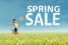 Woman jumps with spring sale clouds Stock Photo