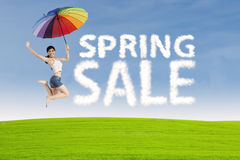 Woman jumps with spring sale sign Royalty Free Stock Photo