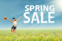 Woman jumps with spring sale sign. Excited woman jumping on the park with cloud design of spring sale sign Royalty Free Stock Image