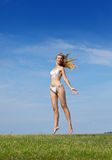Woman jumps in a summer green field Royalty Free Stock Image
