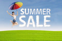 Woman jumps with summer sale sign Stock Images