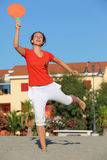 Woman jumps with tennis racket on beach Stock Photo