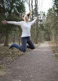 The woman jumps on the track in the early spring wood Royalty Free Stock Photos