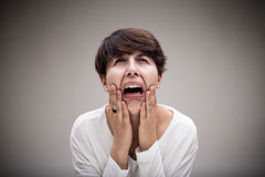 Woman just wanting to cry because of her anguish. Woman weeping in an exaggerated expression of sadness and despair stock image