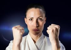 Woman in karate suit against blue flare Royalty Free Stock Photography