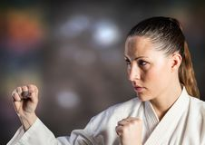 Woman in karate suit posing against blurry brown background Stock Photos