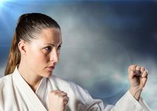Woman in karate suit posing against clouds and flares Stock Photo