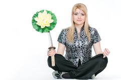 Woman with katana meditating in lotus pose Stock Photo