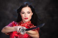 Woman and katana/sword. Pretty kimono woman in action with katana/sword Royalty Free Stock Image