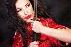 Woman and katana/sword. Pretty female katana warrior on dark background Royalty Free Stock Photo