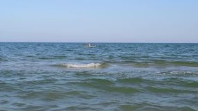 Woman in kayak on blue sea. Unidentifiable woman in yellow kayak far off on blue sea stock video