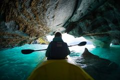 Woman with kayak explores the Marble Caves. Paddles inside the cave with interesting patterns on the walls and crystal clear water. Caves are located on the royalty free stock photo