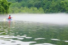Woman in kayak. Woman paddles across water into fog Stock Photo