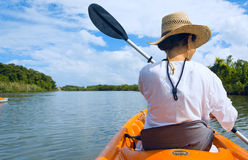 Woman in a kayak. Woman paddling a kayak on a river Stock Photos