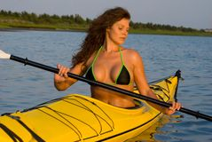 Woman Kayaking. Woman in a bikini paddling the back bay in a yellow kayak stock photography