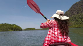 Woman kayaking in beautiful lagoon action camera pov of girl paddling on kayak boat in sea. Back rear view stock footage