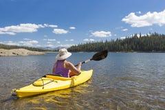 Woman Kayaking on Beautiful Mountain Lake. Stock Photo
