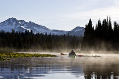 Woman Kayaking On Lake In Morning Mist Royalty Free Stock Image