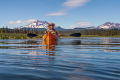 Woman kayaking on mountain lake near Bend, Oregon Stock Images
