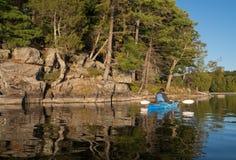 Woman Kayaking on Northern Lake Stock Photo