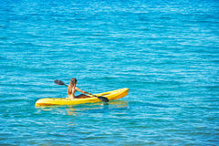 Woman Kayaking in the Ocean on Vacation stock photos
