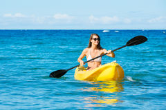 Woman Kayaking in the Ocean on Vacation Stock Images