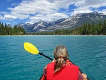 Woman kayaking with red inflatable kayak on Edith Lake, Jasper, Rocky Mountains, Canada. Woman kayaking with red inflatable kayak on turquoise colored Edith Lake royalty free stock photography