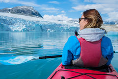 Woman kayaking on Styggvatnet glacier lake near Jostedalsbreen glacier. Royalty Free Stock Photo
