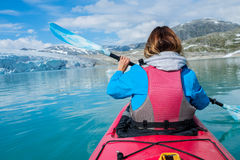 Woman kayaking on Styggvatnet glacier lake near Jostedalsbreen glacier. stock images