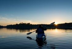 Woman Kayaking at Sunset Stock Image