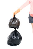 Woman Keep garbage in bag for eliminate. Woman hand carry garbage in plastic bag for eliminate on the white background Royalty Free Stock Photos