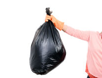 Woman Keep garbage in bag for eliminate. Woman hand carry garbage in plastic bag for eliminate on the white background Stock Image