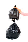 Woman Keep garbage in bag for eliminate. Woman hand carry garbage in plastic bag for eliminate on the white background Stock Photos