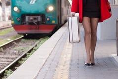 Woman keep luggage at subway. Woman with red coat and heels keep luggage at train subway platform Royalty Free Stock Photos
