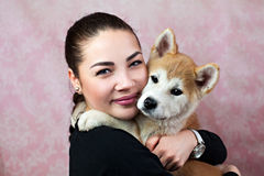 Woman Keeping Akita Puppy Near Her Face Stock Photography