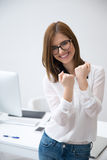 Woman keeping arms raised in office Stock Image