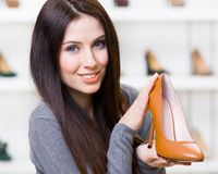 Woman keeping brown heeled shoe Royalty Free Stock Photo