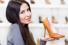 Woman keeping brown high heeled shoe. Portrait of woman keeping brown leather high heeled shoe in shopping center Stock Photography