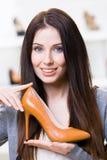 Woman keeping brown stylish shoe Stock Photo