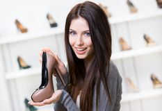 Woman keeping coffee-colored shoe Stock Photos