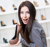 Woman keeping coffee-colored stylish shoe Royalty Free Stock Image