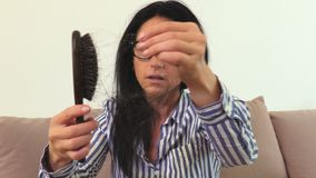 Woman keeping comb with hair in hand.Hair loss concept. In room stock video