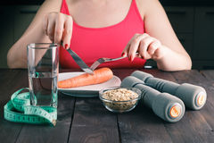 Woman keeping a diet and eating carrot in the kitchen Royalty Free Stock Photos
