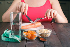 Woman keeping a diet and eating carrot in the kitchen Royalty Free Stock Photo