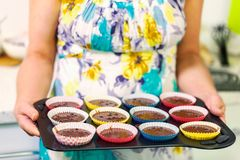 Woman with keeping muffins tray stock photo